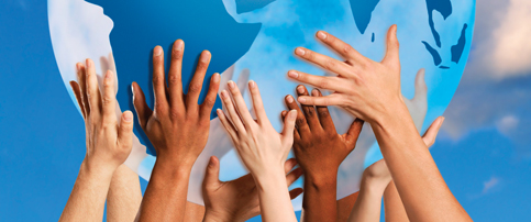 Picture of diverse hands holding up a globe
