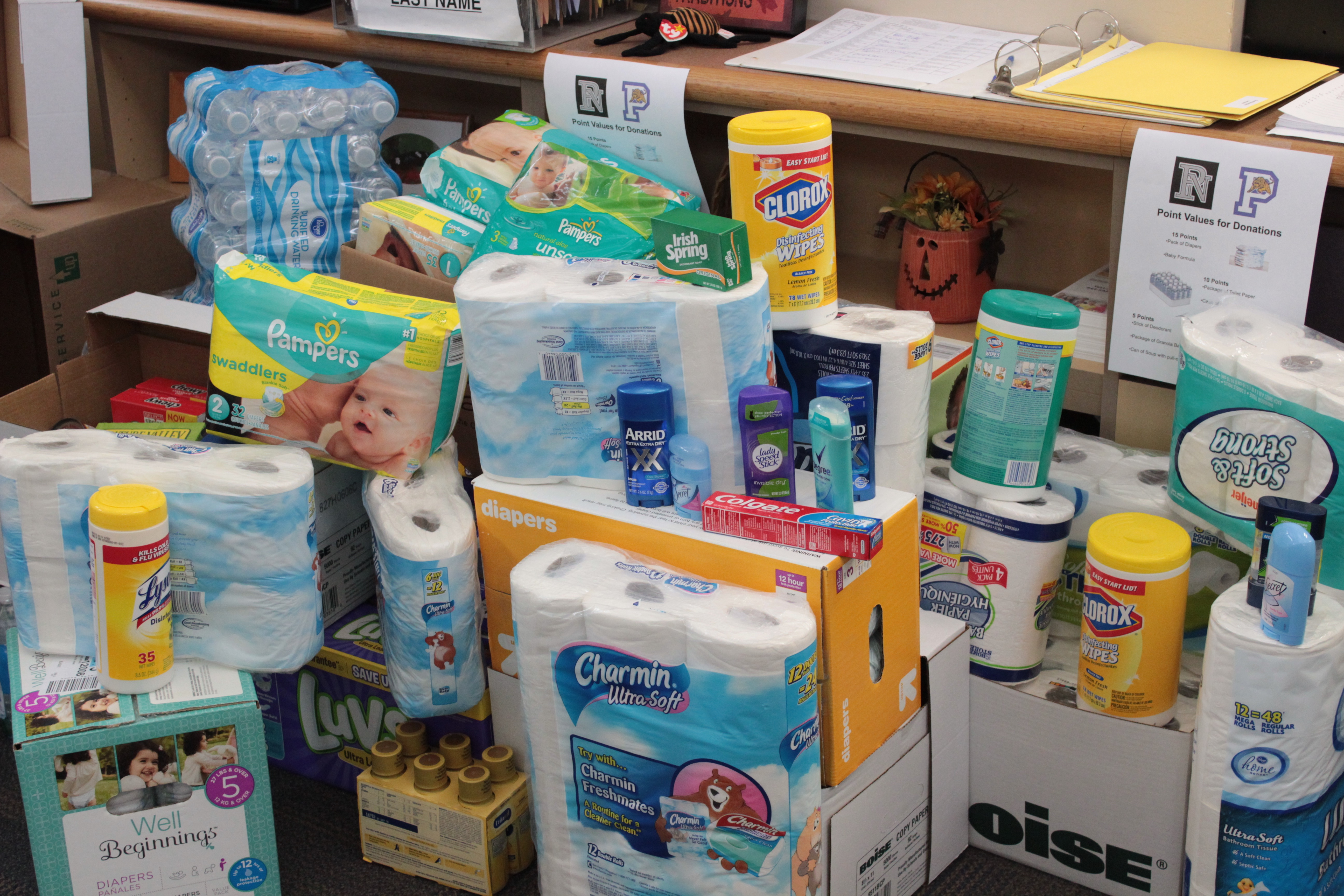 Photo showing the donated items, toilet paper, water, soap