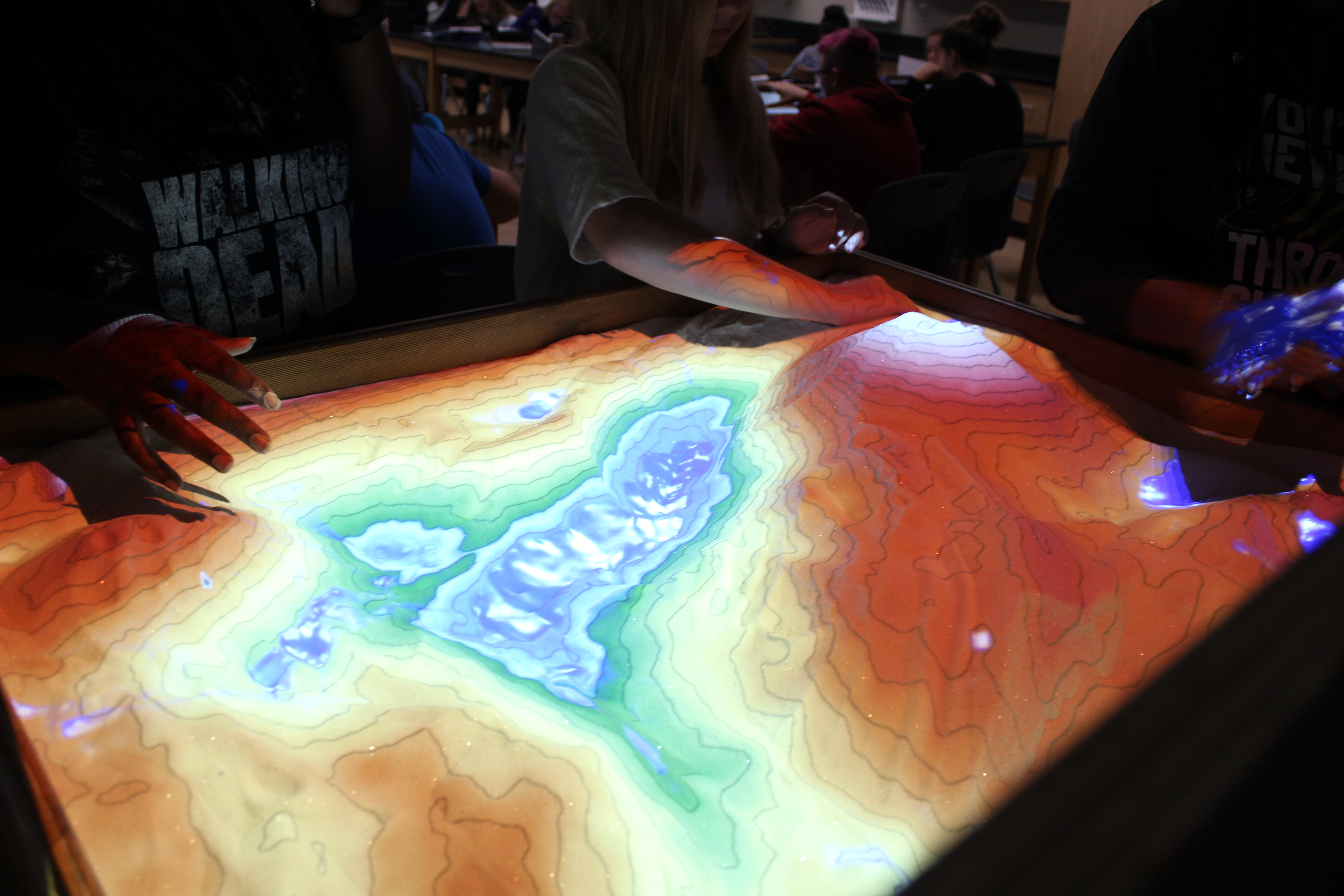 Students playing in colorful, topographic map sandbox